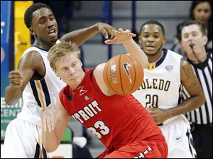 University of Toledo guard Justin Drummond (4) defends against  Detroit forward Evan Bruinsma (33).
