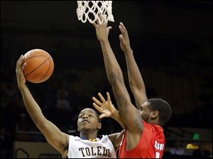 University of Toledo guard Jonathan Williams (1) goes to the net against Detroit guard Anton Wilson (1).