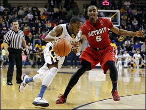 University of Toledo guard Julius Brown (20) drives past Detroit guard Matthew Grant (5).