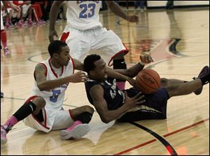 Bowsher's Jason Sandridge forces a jump ball with St. Johns' Anthony Glover Jr.