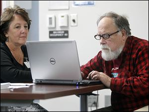 Elizabeth Macino,  a CareNet navigator, helps John Thomas of Toledo sign up for Obamacare during an initial session held on Wednesday at the United Way offices in downtown Toledo.