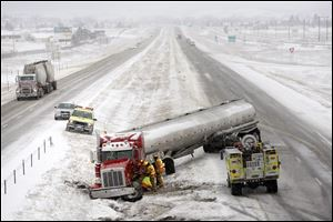 A tanker truck is tended to by firefighters after sliding off the snowy highway near mile marker 48 on Interstate 90 in Piedmont, S.D. Tuesday.