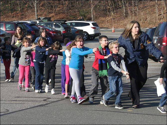 5n5newtownkids Police lead students from Sandy Hook in Newtown, Conn., on Dec. 14, 2012. Recordings of 911 calls reveal the raw emotion of those trapped in the school.