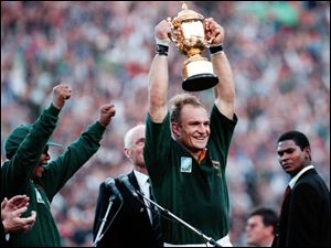 In this June 24, 1995, photo, South African rugby captain Francios Pienaar, center, raises the trophy after receiving it from South African President Nelson Mandela, left, who wears a South African rugby shirt, after they defeated New Zealand in the final 15-12 at Ellis Park, Johannesburg. Mandela strode onto the field wearing South African colors and bringing the overwhelmingly white crowd of more than 60,000 to its feet. They chanted