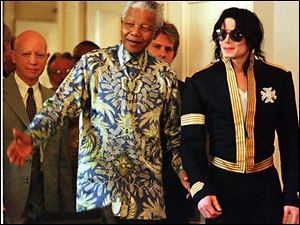 In this March 23, 1999 photo, South African President Nelson Mandela, left, stands with American pop singer Michael Jackson at a news conference in Cape Town where Jackson announced dates for two concerts in June of which profits will go to various funds including the Nelson Mandela Children's Fund.