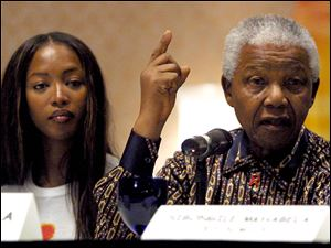 In this July 30, 2001 photo, former President of South Africa, Nelson Mandela, right, speaks during a press conference alongside British model Naomi Campbell in Barcelona, Spain, before the 'Frock and Roll'  benefit concert to raise money for the Nelson Mandela Children's Fund.