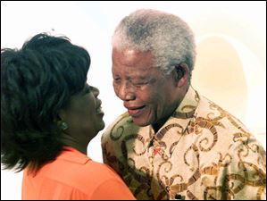 In this Dec. 6, 2002 photo, former South African President Nelson Mandela, right, and American talk show host Oprah Winfrey embrace.