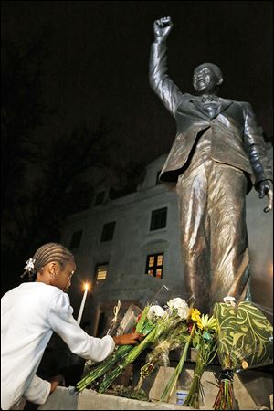 Flowers are placed at a statue of Nelson Mandela at South Africa's U.S. embassy. Participants in his 1990 Detroit appearance remember the excitement.