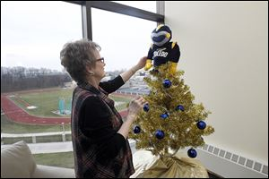 Jacki Way, admires the Christmas tree that she and a colleague decorated and topped with a Rocky Golf Head Cover for a driver for sale at UT  in the foyer of the athletics office.