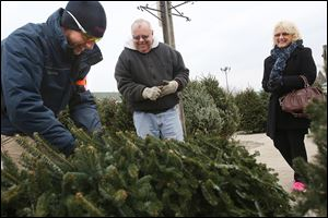 Dylan Willits, left, a sales associate at The Andersons, jokes with Roger and Sherri Kerner of West Toledo before taking their newly chosen tree to be wrapped up and trimmed on the Christmas tree lot at the company's store in West Toledo. The store began the season with 1,190 fraser fir trees for sale.