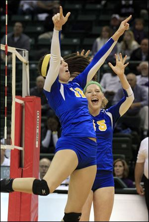 St. Ursula's Lauren Daudelin, 12, and Elizabeth Coil, 15, celebrate another point  during a Div. I state semi-final volleyball game on Nov. 7, 2013 at the Nutter Center in Fairborn, Ohio.