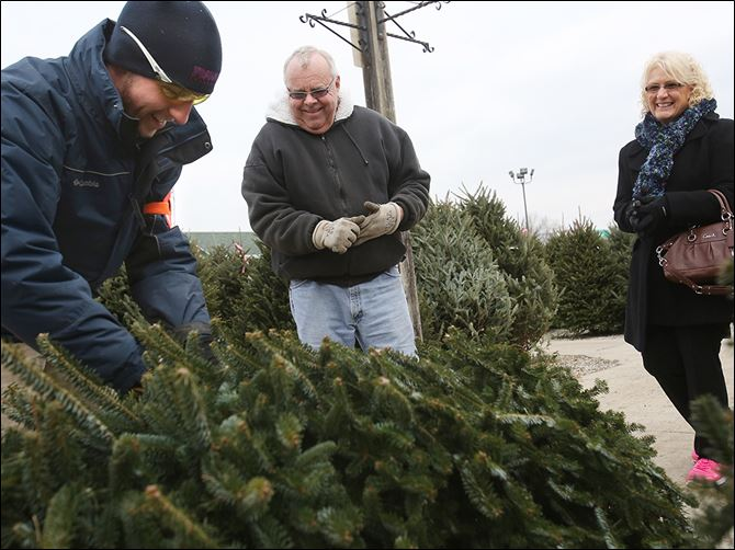 b6xmas-3 Dylan Willits, left, a sales associate at The Andersons, jokes with Roger and Sherri Kerner of West Toledo before taking their newly chosen tree to be wrapped up and trimmed on the Christmas tree lot at the company's store in West Toledo. The store began the season with 1,190 fraser fir trees for sale.