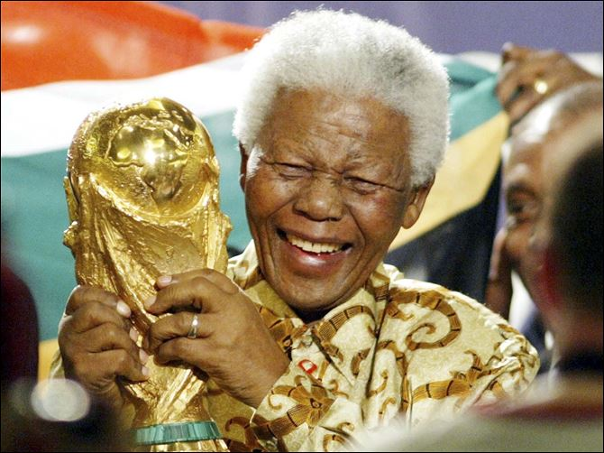 Mandela-Power Of Sports In this May 15, 2004 photo, former South African President Nelson Mandela lifts the World Cup trophy in Zurich, Switzerland, after FIFA's executive committee announced that South Africa would host the 2010 FIFA World Cup soccer tournament.