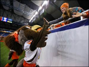 Bowling Green State University mascot Frieda the Falcon high-fives a fan before the Falcons play Northern Illinois University.