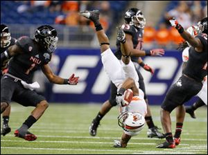 Bowling Green State University player Ronnie Moore (5) is upended by Northern Illinois University player Jimmie Ward (15) on a kick return during the first quarter.