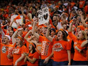 Bowling Green State University students cheer on the Falcons against Northern Illinois University player during the first quarter.