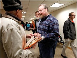David Jackson, president of the BGSU Faculty Association, right, speaks with Art Brecher, left, a BGSU faculty member  during a rally in the hallway.