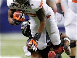 Bowling Green State University player Travis Greene (13) is tackled by Northern Illinois University player Boomer Mays (45).