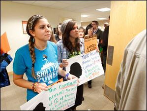 Students Jessica Echales, left, from Chicago, and Madison Thomas, right, from Solon, march into the board meeting.