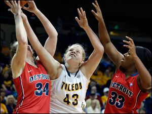 University of Toledo center Sophie Reecher (43) battles Detroit forwards Megan Galloway (34) and DeVonna Bradford (33) for a rebound.