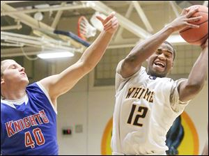 Whitmer's Kemontrece Collins, right, pulls down a rebound over St. Francis' Jacob Lang.