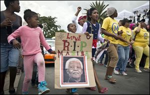 "A young girl with a placard showing the face of Nelson Mandela and referring to his clan name ""Madiba"", marches with others to celebrate his life, in the street outside his old house in Soweto, Johannesburg."