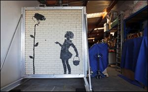 """Flower Girl,"" a delicate stencil on a massive brick wall by popular street artist Banksy, is displayed in a warehouse in the greater Los Angeles area Wednesday,."