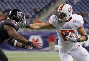 Bowling Green State University player Alex Bayer (82) gets a hand in the face of Northern Illinois University player Boomer Mays (45) during the second quarter.