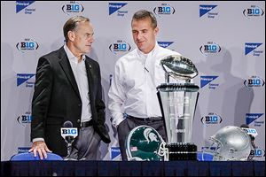 Michigan State coach Mark Dantonio, left, talks with OSU coach Urban Meyer during a news conference Friday in Indianapolis. Their teams will meet today for the Big Ten championship.