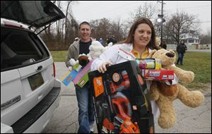 Ben and Tiffany Decker of Maumee carry toys to the WTVG-TV toy drive.