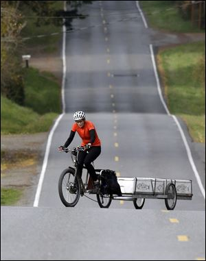 Heidi Lappetito zigzags her cargo bike across the road to help moderate the steep hill while hauling a trailer loaded with frozen salmon near Port Townsend, Wash.