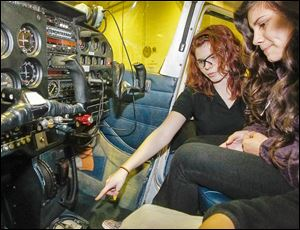 Junior Heaven Ward, left, shows Marissa Cockerill, right, from Toledo, the controls inside a Cessna 172 during a visit by TPS ninth graders to the Aviation Center at Toledo Express Airport to see if they are interested in enrolling in the district's three-year Aviation Technician Program.
