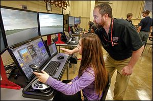 Start Freshman Mya Sanchez, left, listens as Rich Naves, training director, right, gives her a lesson on the simulator during a visit by TPS ninth graders to the Aviation Center to see if they are interested in enrolling in the district's 3-year Aviation Technician Program.