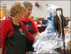 Event volunteers Pat Skreuz, left, and Sandy Davidson, both of Maumee, take a look at some of the auction items.