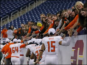 Bowling Green State University players high-five fans after defeating Northern Illinois University during their MAC Championship football.