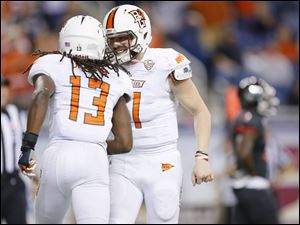Bowling Green State University players Travis Greene (13) and Matt Johnson (11) celebrate after connecting for a touchdown against Northern Illinois University player during the fourth quarter.