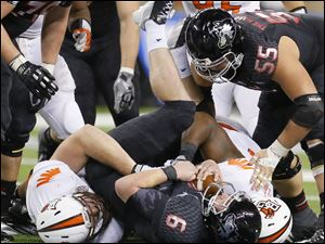 Bowling Green State University players Ted Ouellet (93) and Taylor Royster (51) sack Northern Illinois University quarterback Jordan Lynch during the fourth quarter.