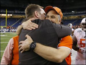 Bowling Green State University athletic director Chris Kingston, left, hugs head coach Dave Clawson.