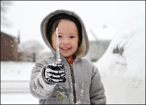 Jared Shepard, 5, plays in the snow in his front yard after several inches of snow and ice blanketed the area Friday in Van Buren, Ark.