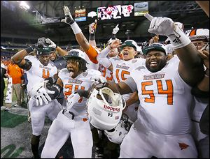 "Bowling Green State University players Jordan Hopgood (4) Jerry ""Boo Boo"" Gates (24) and Mike Minns (54) celebrate with teammates after the Falcons defeated Northern Illinois University 47-27 during the  MAC Championship at Ford Field in Detroit, Friday."