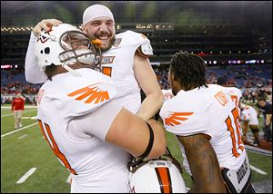 Bowling Green's Matt Johnson is bear-hugged by teammate Christian Piazza as they celebrate their 47-27 win over Northern Illinois. Johnson threw for five touchdowns and 393 yards.