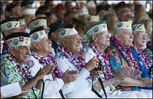 Pearl Harbor survivors watch a vintage World War II airplane fly over Pearl Harbor at the ceremony commemorating the 72nd anniversary of the attack on Pearl Harbor today in Honolulu.