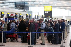Passengers queue at the flight check-in desk to re-book tickets at London's Heathrow Airport Terminal 5 after a