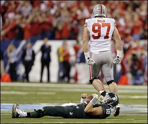 Ohio State's Joey Bosa (97) reacts after sacking Michigan State's Connor Cook during the first half in Indianapolis.