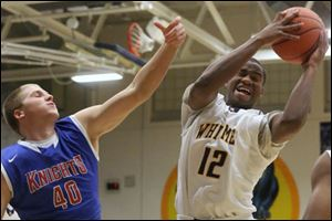 Whitmer's sophomore Kemontrece Collins (12) pulls down a rebound over St. Francis' junior Jacob Lang (40) during the first quarter of the Friday, Dec. 6, 2013, matchup at Whitmer. Whitmer won, 54-50.