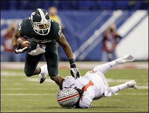Michigan State's Jeremy Langford, left, is tackled by Ohio State's Bradley Roby (1) during the Big Ten  championship game.