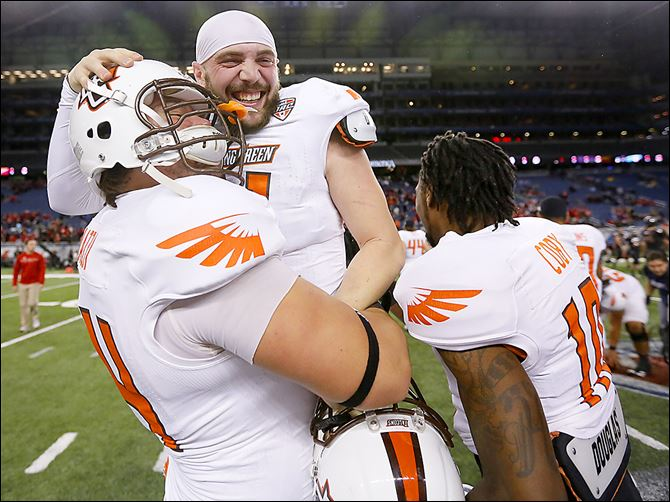 07s7falconswin Bowling Green's Matt Johnson is bear-hugged by teammate Christian Piazza as they celebrate their 47-27 win over Northern Illinois. Johnson threw for five touchdowns and 393 yards.