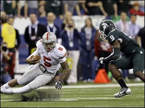 Ohio State's Braxton Miller (5) is tackled by Michigan State's Isaiah Lewis (9) during the first half.