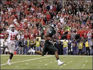 Michigan State's Jeremy Langford (33) runs past Ohio State's Doran Grant (12) for a 26-yard touchdown run.
