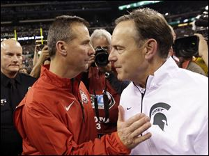 Michigan State head coach Mark Dantonio is congratulated by Ohio State head coach Urban Meyer following the game.